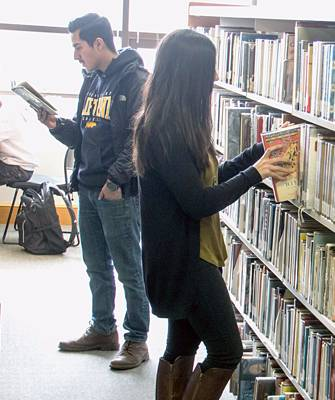 students reading in book stacks in the library